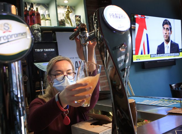 A pub worker pulls a pint in the Tib Street Tavern in Manchester