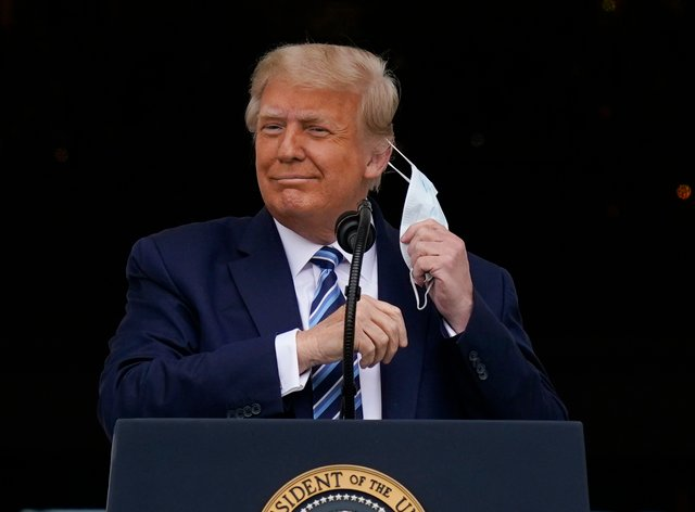Donald Trump removes his face mask