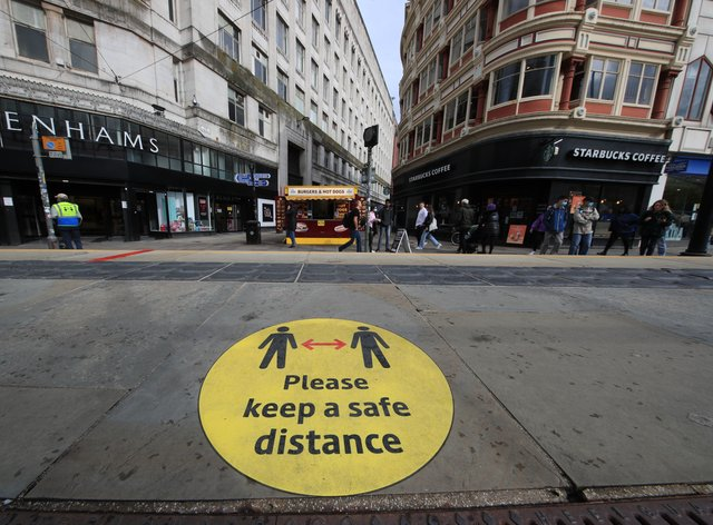 A social distancing guidance sign on the pavement