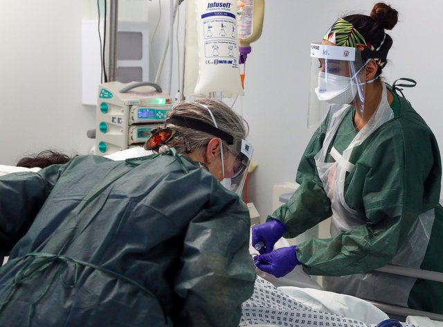 Nurses tend to a patient in an intensive care unit