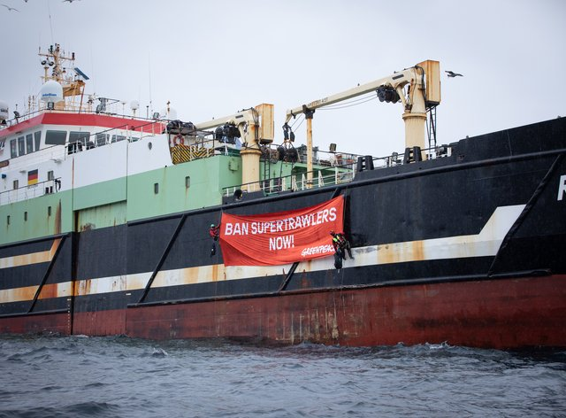 Two Greenpeace UK activists unfurl on the Helen Mary a banner reading 'Ban Supertrawlers Now!'