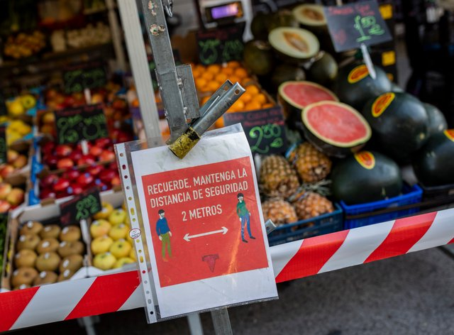 A social distancing sign in a market in Madrid, Spain