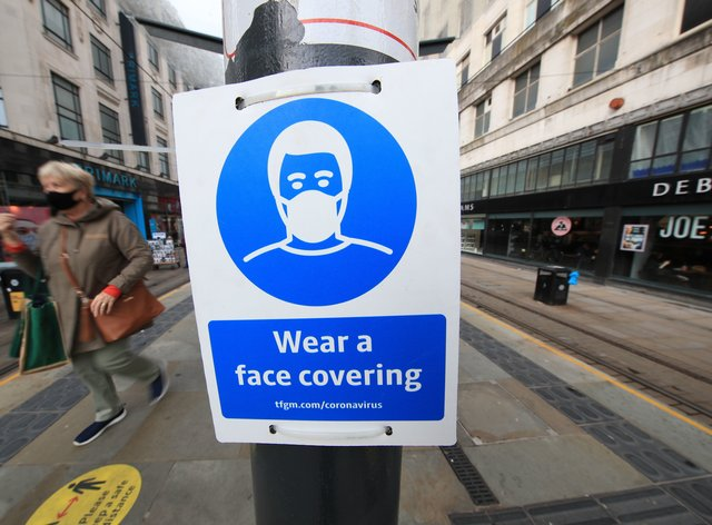 A sign advising on wearing face coverings at a tram stop in Manchester (Danny Lawson/PA)