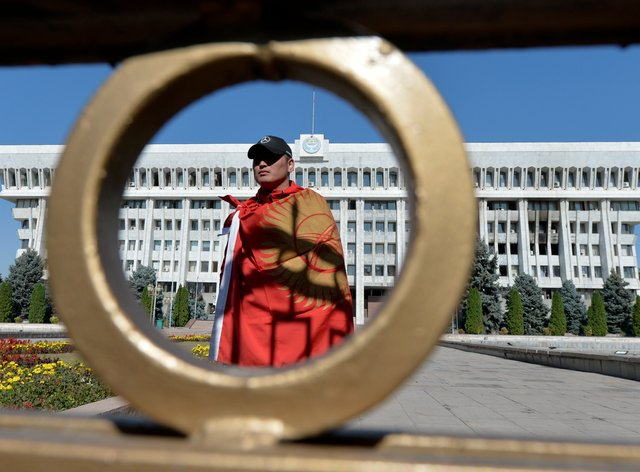 An activist stands in front of the Kyrgyz government headquarters on the central square in Bishkek (Vladimir Voronin/AP)