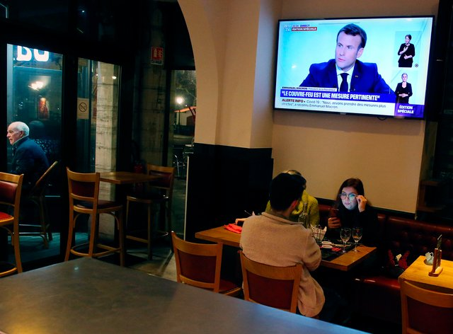 People dine at a restaurant as French President Emmanuel Macron gives an address on television