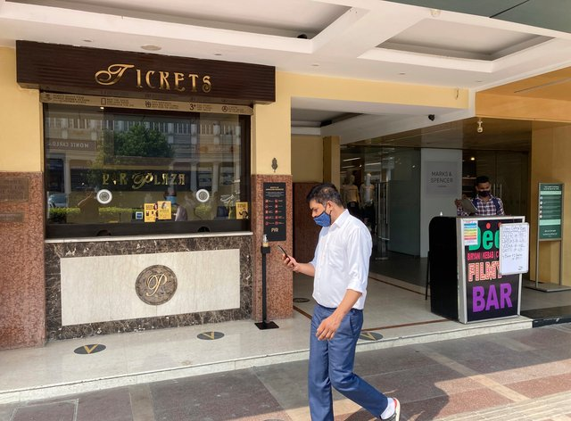 A man wearing a face mask walks past the ticket counter of a cinema in New Delhi (Shonal Ganguly/AP)