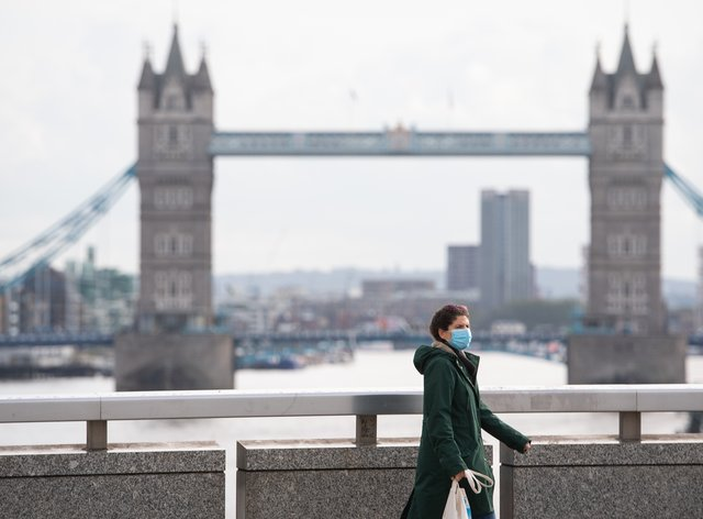 A woman wearing a protective face mask walks over London Bridge in central London, with Tower Bridge in the distance
