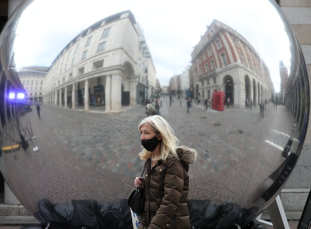 A woman wearing a protective face mask is reflected on the surface of a sculpture in Covent Garden, London