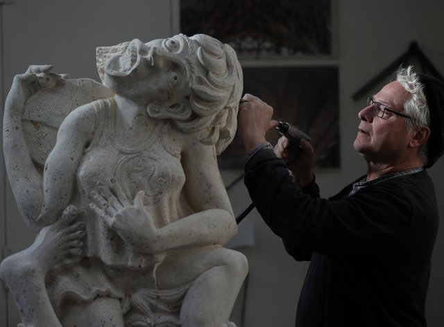 Master mason Pascal Mychalysin works on a gargoyle holding a cheese, to represent the Cheese Rollers of Gloucestershire, as part of a project for Gloucester Cathedral