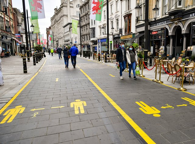 People wear face coverings as they walk along socially distanced floor markings in Cardiff (Ben Birchall/PA)