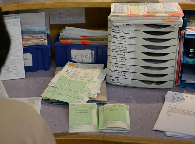 A receptionist sorts prescriptions at GP centre