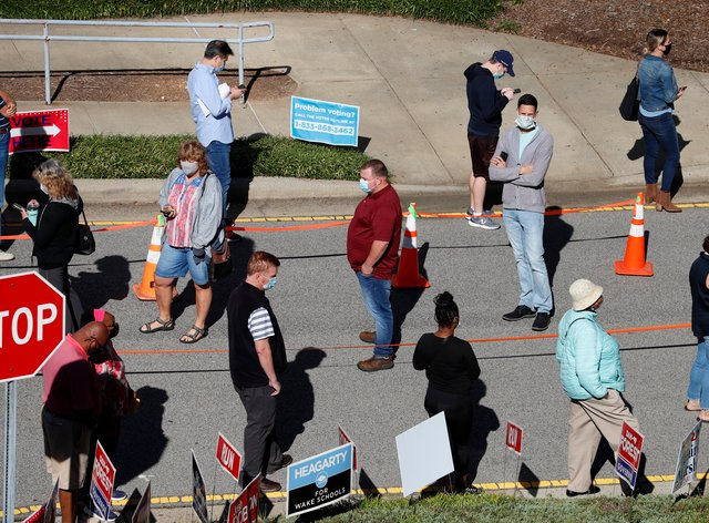 Voters wait in line outside the Herbert C. Young Community Centre in Cary, North Carolina (Ethan Hyman/AP)