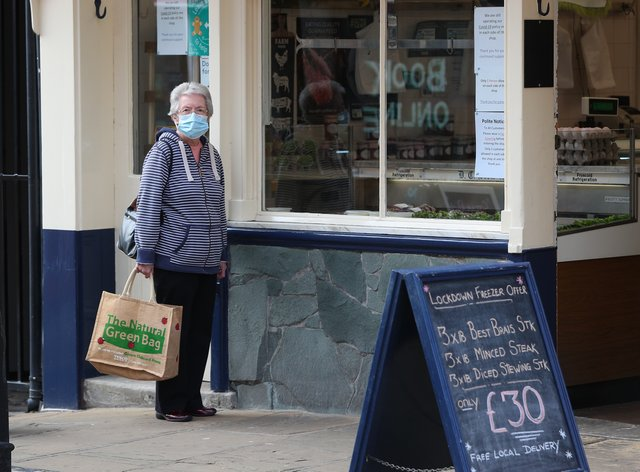 A woman waits outside a butchers in Ormskirk, Lancashire, that is offering a 'lockdown freezer offer'