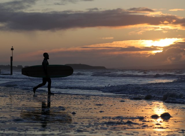 A surfer on Boscombe beach in Dorset