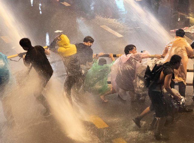 Pro-democracy demonstrators face water cannons as police try to clear the protest venue in Bangkok, Thailand (Gemunu Amarasinghe/AP)
