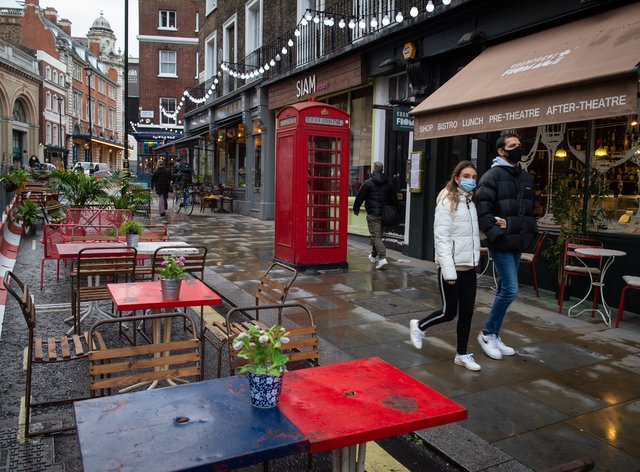 People wearing face masks walk pass empty tables outside bars and restaurants in Covent Garden, in central London (Dominic Lipinski/PA)