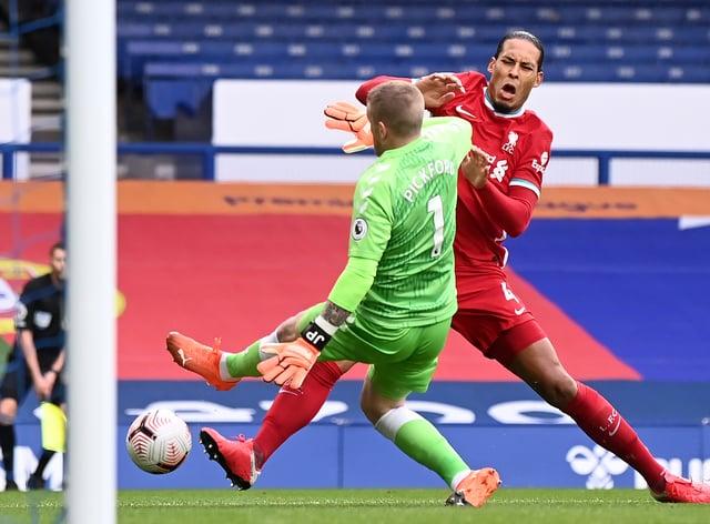 Liverpool's Virgil van Dijk is challenged by Everton goalkeeper Jordan Pickford