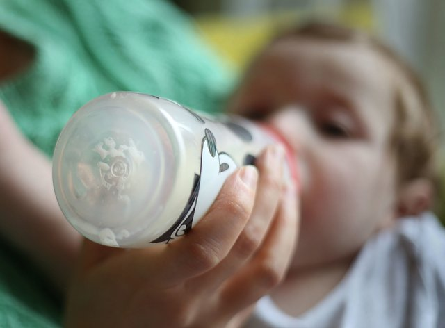 An eight month old baby boy drinking from a bottle