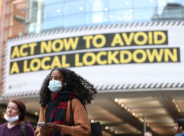 A woman wearing a face mask walks through Manchester (Martin Rickett/PA)