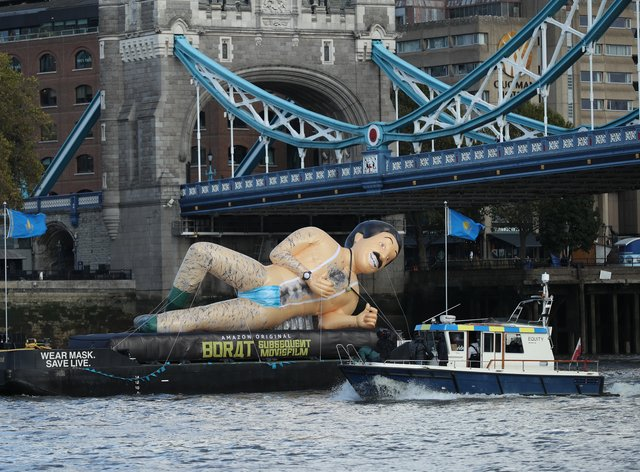 A giant inflatable in the shape of Borat floats on a barge beneath Tower Bridge