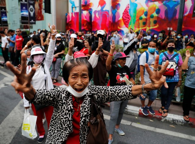 Pro-democracy protesters gather, flashing three-fingered salutes near a main shopping district in Bangkok