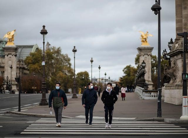 People wearing masks, walk in the Invalides district of Paris (Lewis Joly/AP)