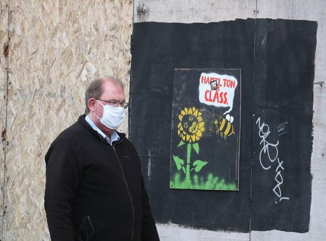 A man walks past graffiti in Hamilton