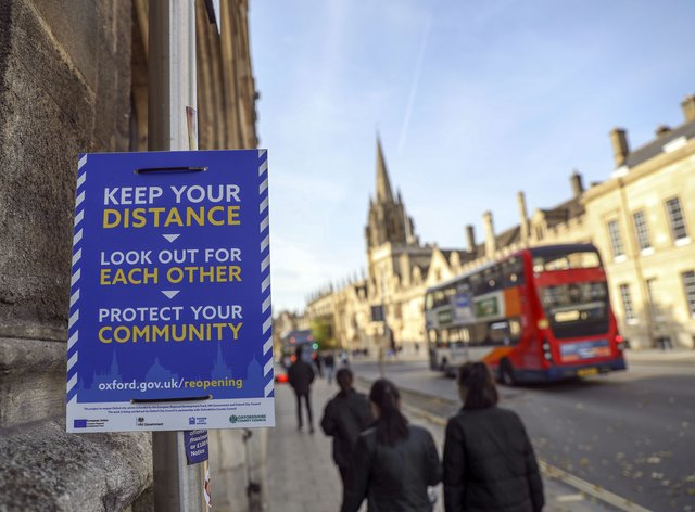 Students walk past a Covid-19 sign in Oxford