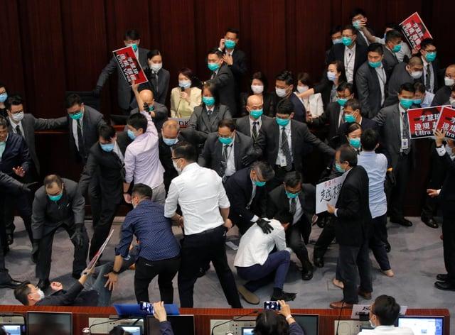 Pro-establishment politician, Starry Lee, centre, speaks as pan-democratic legislators scuffle with security guards and pro-China legislators in Hong Kong, Friday, May 8, 2020