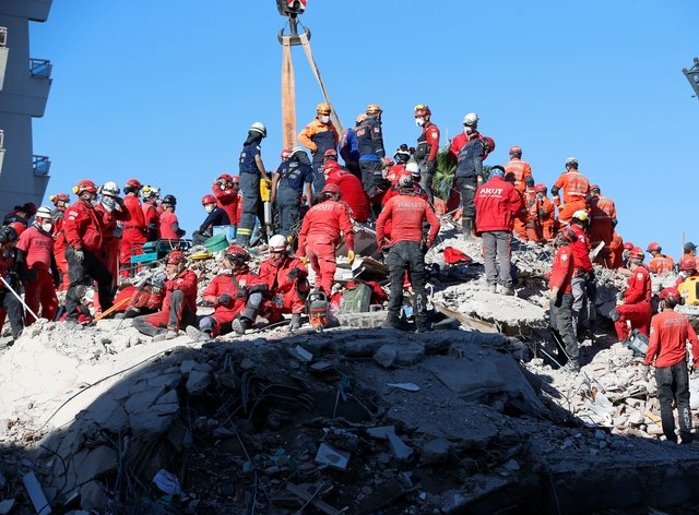 Members of rescue services search in the debris of a collapsed building for survivors in Izmir, Turkey