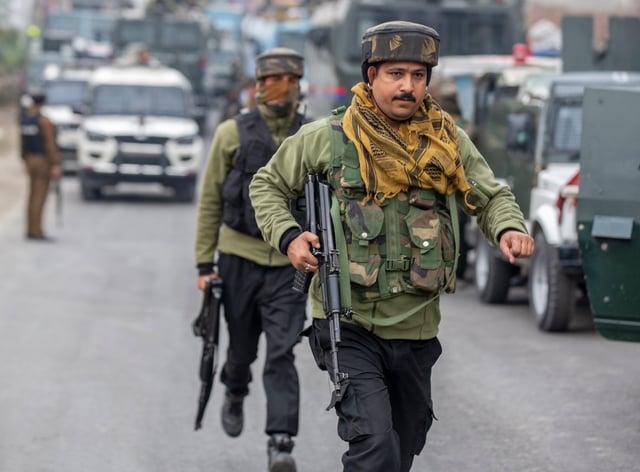 Indian police men rush towards their armoured vehicle near the site of a gun battle on the outskirts of Srinagar (Dar Yasin/AP)