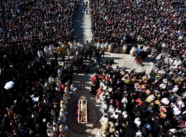 Thousands gathered by an open coffin with Bishop Amfilohije's body during the liturgy and and funeral outside the main temple in the capital Podgorica, Montenegro (Risto Bozovic/AP)