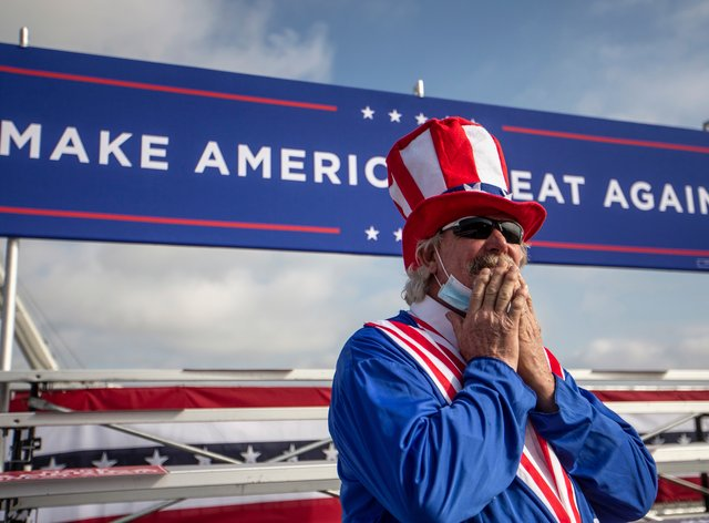 A Trump supporter stands under a Make America Great Again banner