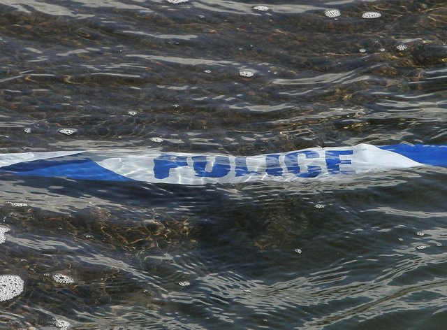 Police tape floats in the sea
