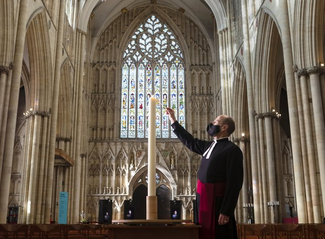 Canon Michael Smith lights a candle during York Minster's Season of Remembrance