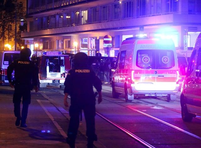 Police officers walk near ambulances at the scene after gunshots were heard in Vienna
