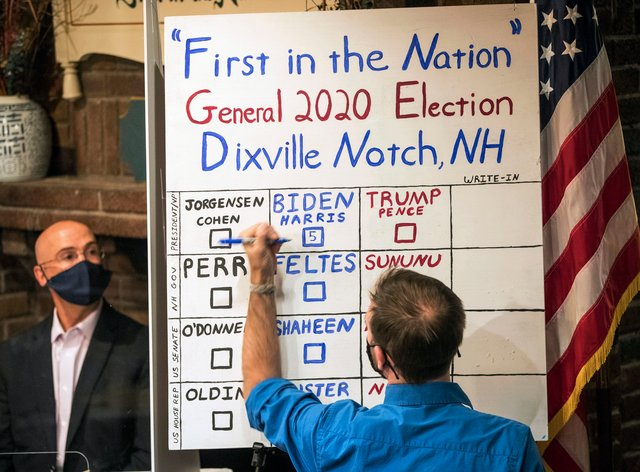A man tallies the votes from the five ballots cast just after midnight