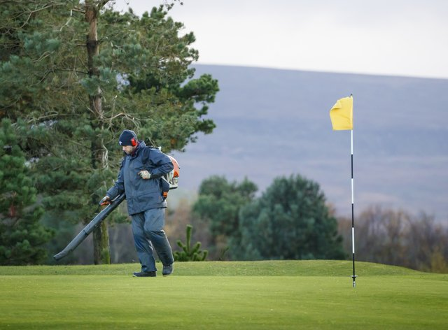 A groundsman blows leaves off a golf course