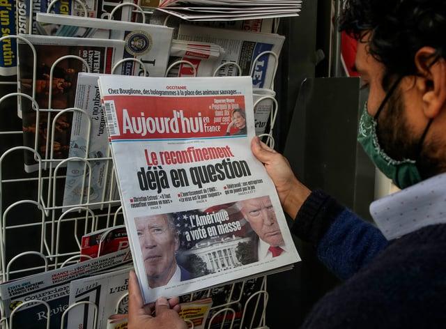 A man reads a newspaper in Paris