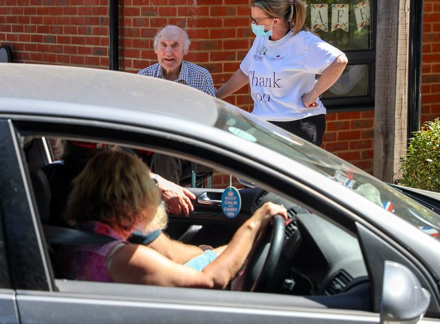 A care home resident meets relatives on a drive-through visit