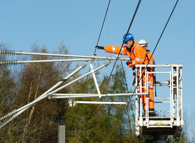 Engineers work on overhead cables