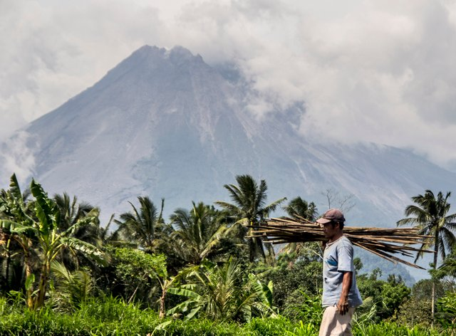 A farmer walks on his field as Mount Merapi is seen in the background (Slamet Riyadi/AP)
