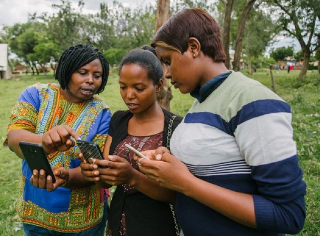 FGM survivor and activist Rhobi Samwelly (left) with local volunteers in a Tanzanian village using opensource mapping to quickly reach girls at risk of being cut (Hope for Girls and Women/PA)