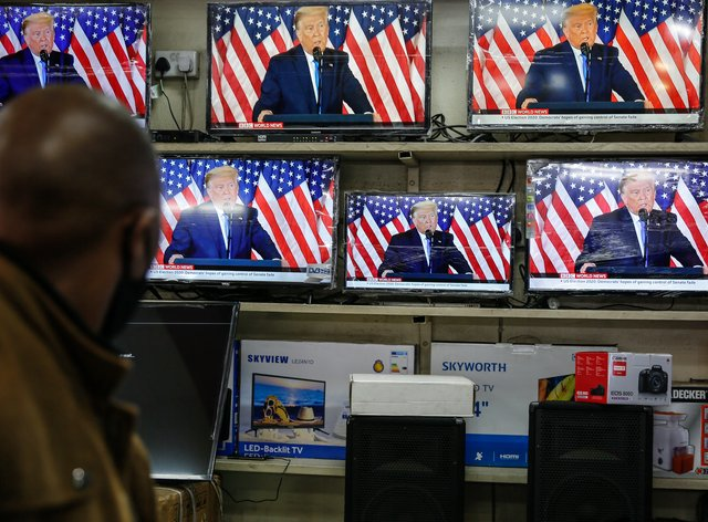 A customer watches Trump