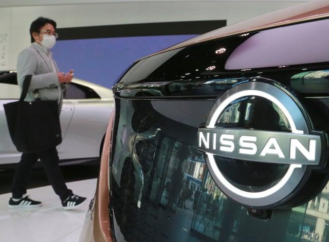 A visitor walks past a car at Nissan showroom in Tokyo (Koji Sasahara/AP)