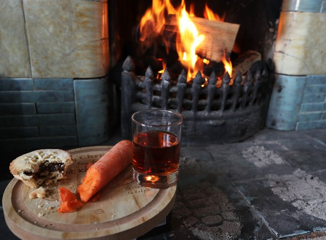 Amince pie, glass of sherry and a carrot for a reindeer is left by a fireplace (Owen Humphreys/PA)