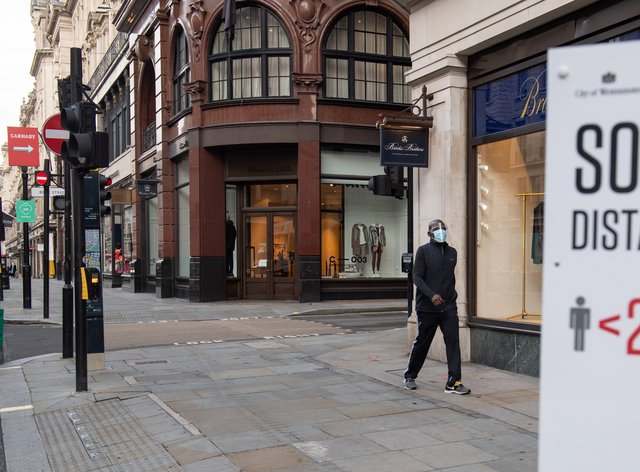 A man wearing a protective visor passes closed shops on Regent Street