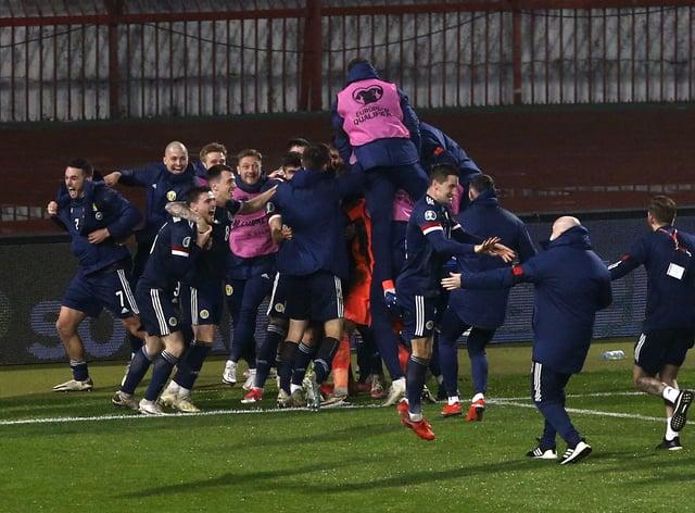 The Scotland players descend on David Marshall