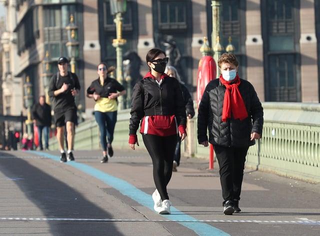 People wearing face masks walking along Westminster Bridge