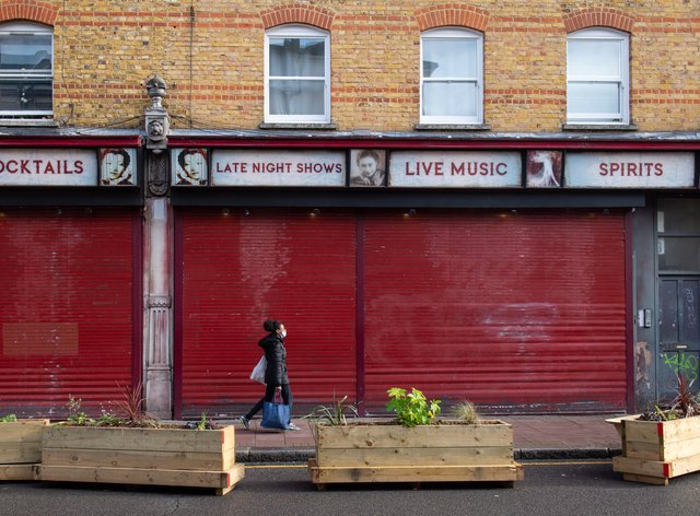 A woman passes a shuttered bar in Brixton, south London